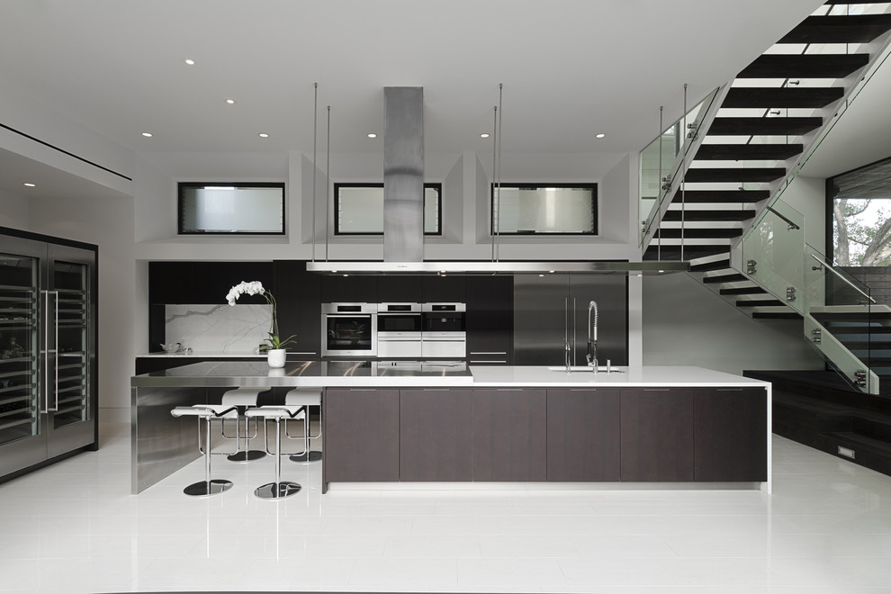 Example of a trendy galley open concept kitchen design in Houston with stainless steel appliances, an undermount sink and flat-panel cabinets