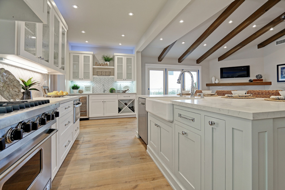 Beach style u-shaped light wood floor open concept kitchen photo in Los Angeles with a farmhouse sink, shaker cabinets, white cabinets, white backsplash, subway tile backsplash, stainless steel appliances and an island