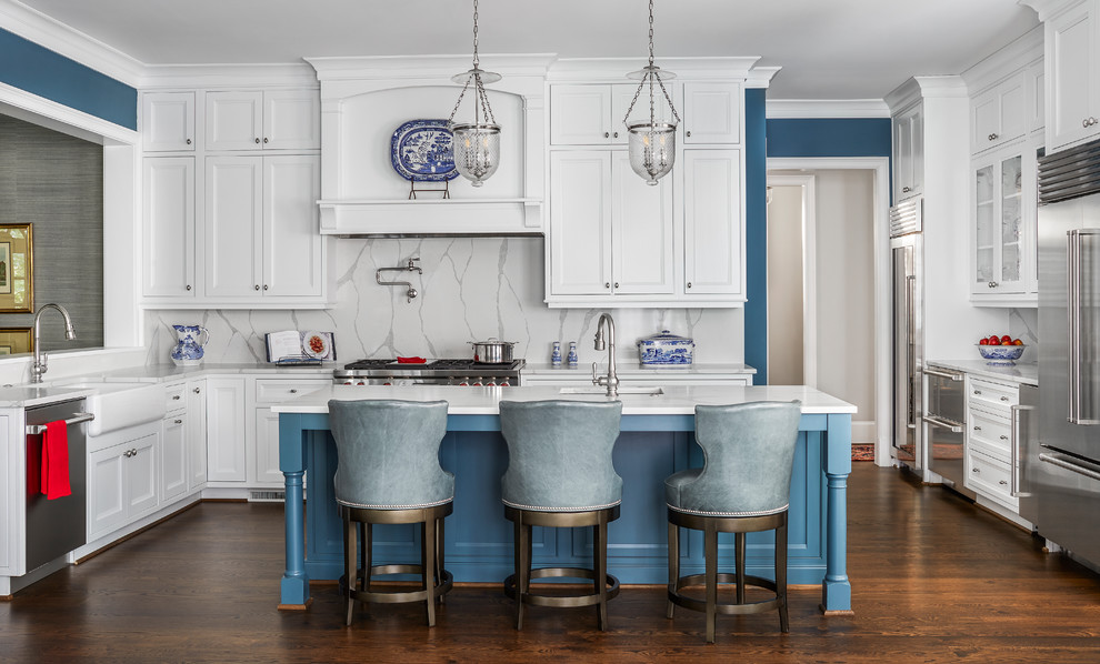 Example of a classic u-shaped dark wood floor and brown floor kitchen design in Atlanta with a farmhouse sink, recessed-panel cabinets, white cabinets, wood countertops, gray backsplash, stone slab backsplash, stainless steel appliances, an island and white countertops