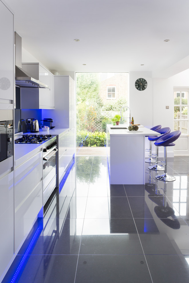 Kitchen - contemporary kitchen idea in London with an undermount sink, flat-panel cabinets, white cabinets, black backsplash and stainless steel appliances