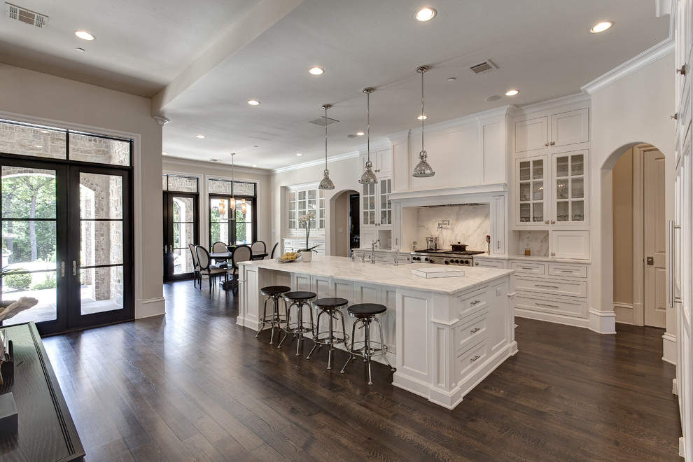 Example of a classic dark wood floor eat-in kitchen design in Dallas with recessed-panel cabinets, white cabinets, white backsplash and stone slab backsplash