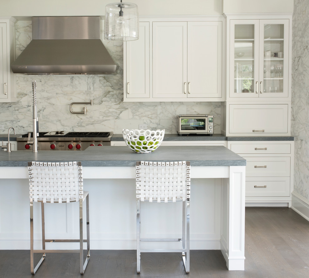 Eat-in kitchen - mid-sized transitional galley medium tone wood floor and gray floor eat-in kitchen idea in New York with recessed-panel cabinets, white cabinets, gray backsplash, stainless steel appliances, an island, marble backsplash, a farmhouse sink and quartz countertops