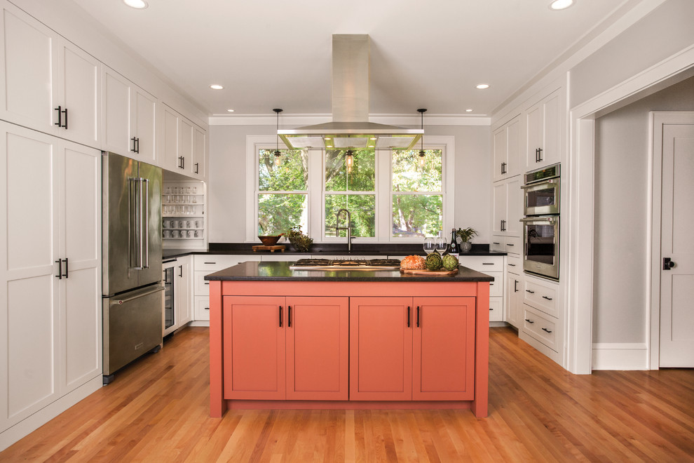 Example of a mid-sized transitional u-shaped medium tone wood floor and brown floor kitchen design in Minneapolis with shaker cabinets, orange cabinets, stainless steel appliances, an island, black countertops, an undermount sink and solid surface countertops
