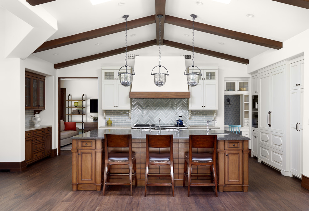 Kitchen - mediterranean l-shaped dark wood floor kitchen idea in Los Angeles with recessed-panel cabinets, white cabinets, gray backsplash, subway tile backsplash, paneled appliances and an island