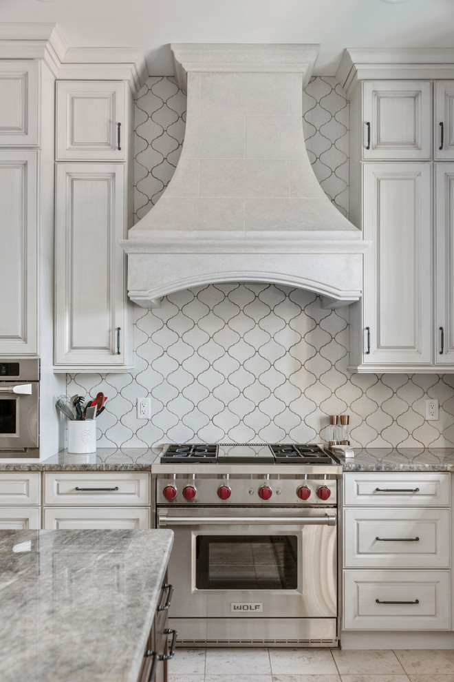 Example of a large tuscan u-shaped ceramic tile and beige floor open concept kitchen design in Tampa with a farmhouse sink, recessed-panel cabinets, beige cabinets, granite countertops, white backsplash, ceramic backsplash, stainless steel appliances, an island and gray countertops