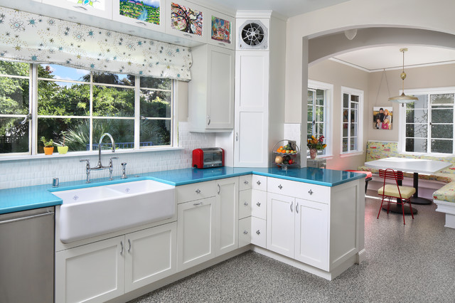 Inspiration for a mid-sized transitional u-shaped linoleum floor enclosed kitchen remodel in San Francisco with a farmhouse sink, shaker cabinets, white cabinets, white backsplash, stainless steel appliances and turquoise countertops