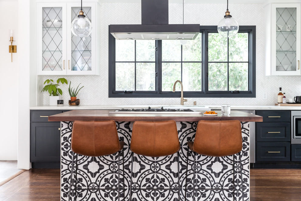 Tuscan galley medium tone wood floor and brown floor eat-in kitchen photo in Sacramento with a farmhouse sink, glass-front cabinets, white cabinets, marble countertops, white backsplash, marble backsplash, an island, white countertops and stainless steel appliances
