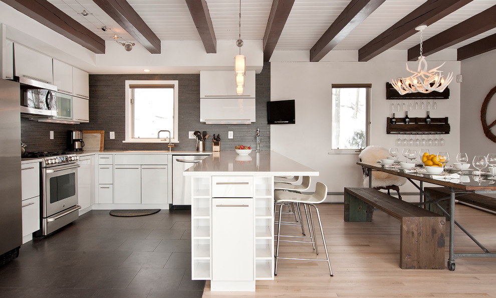 Trendy ceramic tile eat-in kitchen photo in New York with an undermount sink, flat-panel cabinets, white cabinets, quartz countertops, gray backsplash, ceramic backsplash and stainless steel appliances