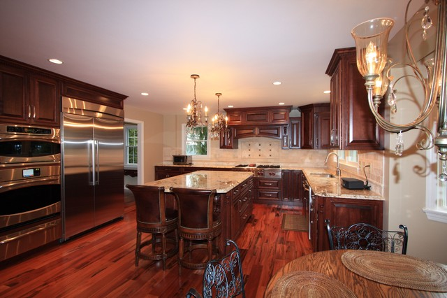 Eat-in kitchen - mid-sized traditional u-shaped medium tone wood floor eat-in kitchen idea in Other with an undermount sink, shaker cabinets, dark wood cabinets, granite countertops, beige backsplash, ceramic backsplash, stainless steel appliances and an island