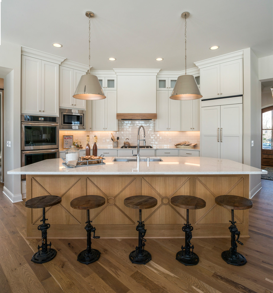 Example of a transitional galley medium tone wood floor and brown floor kitchen design in Minneapolis with marble countertops, an island, an undermount sink, shaker cabinets, white cabinets, white backsplash, subway tile backsplash, paneled appliances and white countertops