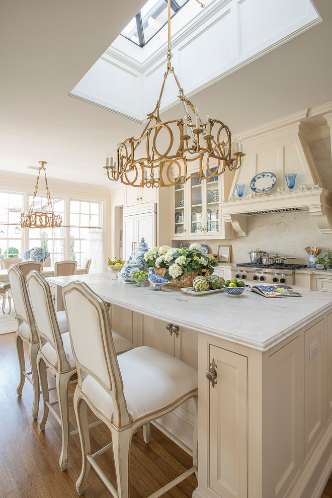 Open concept kitchen - large traditional l-shaped medium tone wood floor and brown floor open concept kitchen idea in Dallas with shaker cabinets, white cabinets, marble countertops, white backsplash, an island, an undermount sink, paneled appliances and marble backsplash