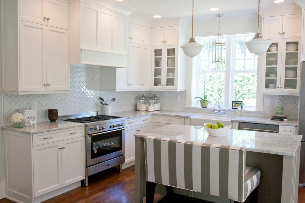 Elegant l-shaped kitchen photo in Salt Lake City with glass-front cabinets, a farmhouse sink, stainless steel appliances, white cabinets and white backsplash