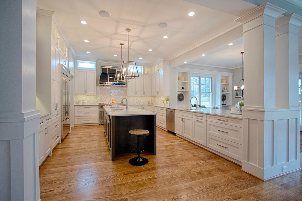 Large transitional u-shaped medium tone wood floor kitchen photo in DC Metro with recessed-panel cabinets, white cabinets, granite countertops, white backsplash, mosaic tile backsplash, stainless steel appliances and an island