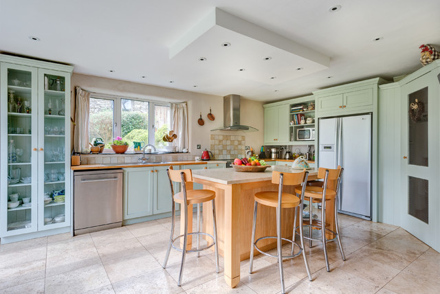 Photo of a medium sized rural l-shaped kitchen in Devon with shaker cabinets, green cabinets, wood worktops, beige splashback and stainless steel appliances.