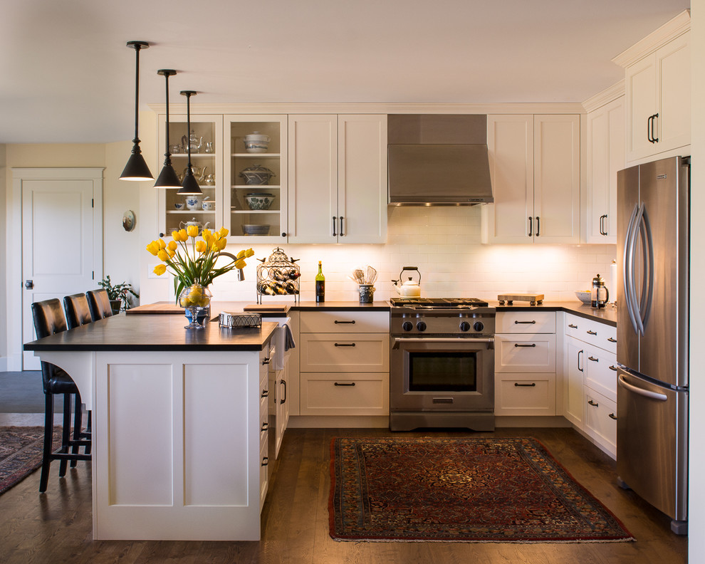 Example of a transitional u-shaped dark wood floor kitchen design in Other with a farmhouse sink, shaker cabinets, white cabinets, white backsplash, subway tile backsplash, stainless steel appliances and a peninsula