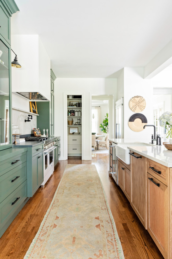 Large transitional galley medium tone wood floor and brown floor open concept kitchen photo in Orlando with a farmhouse sink, shaker cabinets and an island