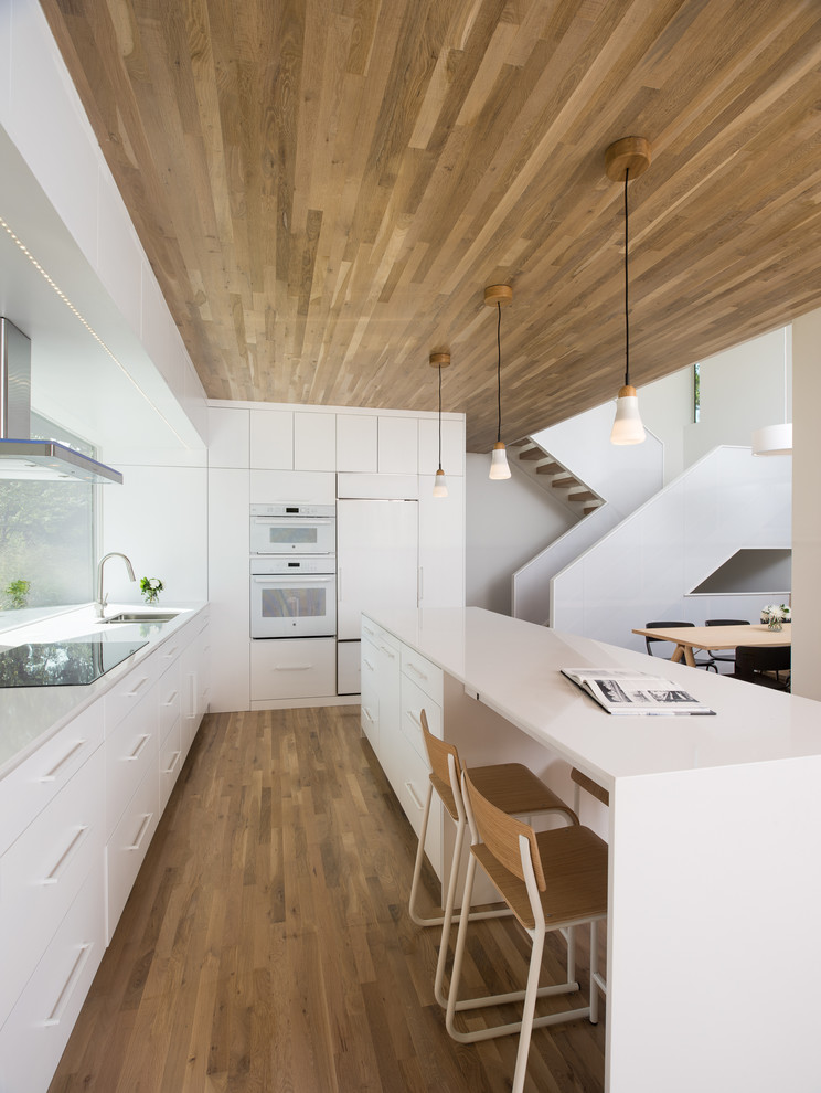 Example of a trendy l-shaped dark wood floor kitchen design in Minneapolis with an undermount sink, flat-panel cabinets, white cabinets, white appliances and an island