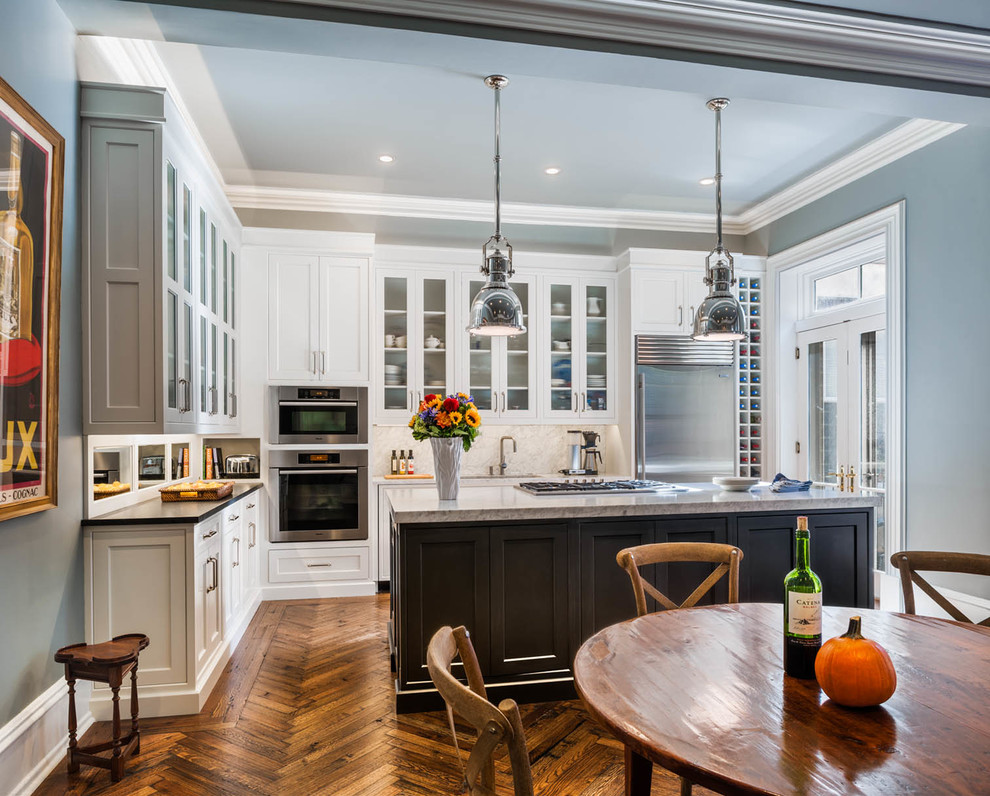 Example of a classic eat-in kitchen design in Philadelphia with shaker cabinets, white cabinets, granite countertops, stainless steel appliances and white backsplash