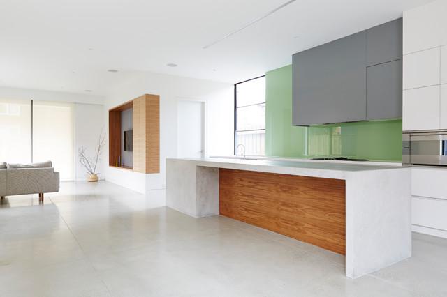 Foto di una cucina minimal di medie dimensioni con lavello a doppia vasca, ante lisce, ante bianche, top in cemento, paraspruzzi verde, paraspruzzi con lastra di vetro, elettrodomestici in acciaio inossidabile, pavimento in cemento e isola