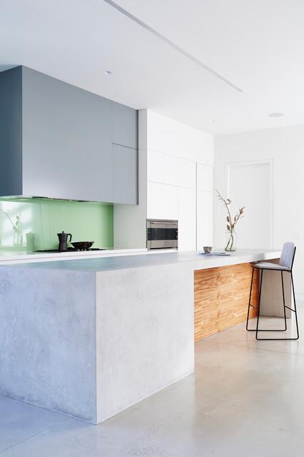 Esempio di una cucina abitabile minimalista di medie dimensioni con ante lisce, pavimento in cemento, isola, ante grigie, paraspruzzi verde, lavello a doppia vasca, paraspruzzi con lastra di vetro e elettrodomestici in acciaio inossidabile