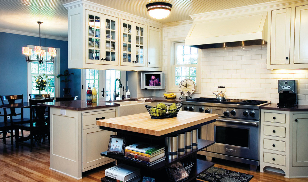 Example of a cottage eat-in kitchen design in Minneapolis with a farmhouse sink, stainless steel appliances, wood countertops, beaded inset cabinets, beige cabinets, white backsplash and subway tile backsplash