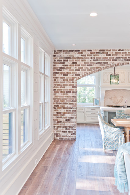 Inspiration for a large beach style u-shaped dark wood floor eat-in kitchen remodel in Jacksonville with a farmhouse sink, beaded inset cabinets, white cabinets, marble countertops, white backsplash, glass sheet backsplash, paneled appliances and an island