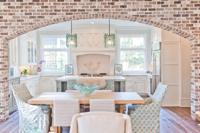 Inspiration for a large beach style u-shaped dark wood floor eat-in kitchen remodel in Jacksonville with a farmhouse sink, beaded inset cabinets, white cabinets, marble countertops, white backsplash, paneled appliances and an island