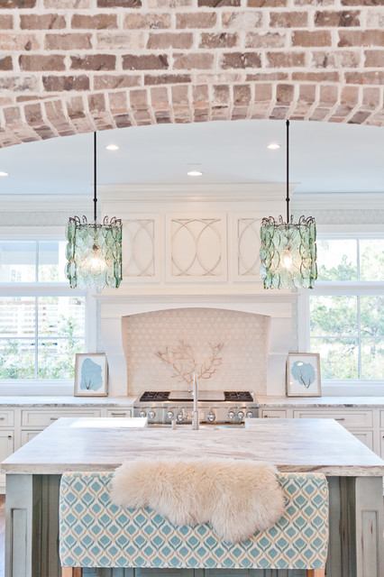 Example of a large coastal u-shaped dark wood floor eat-in kitchen design in Jacksonville with a farmhouse sink, beaded inset cabinets, white cabinets, marble countertops, white backsplash, glass sheet backsplash, paneled appliances and an island