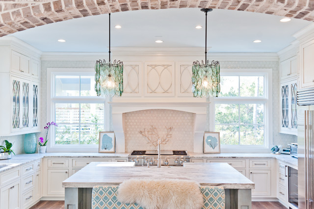 Coastal u-shaped medium tone wood floor kitchen photo in Jacksonville with white cabinets, marble countertops, white backsplash, an island, recessed-panel cabinets and stainless steel appliances