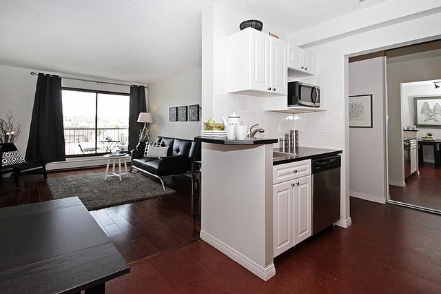 Kitchen - small transitional cork floor kitchen idea in Calgary with a drop-in sink, raised-panel cabinets, white cabinets, white backsplash, ceramic backsplash and stainless steel appliances