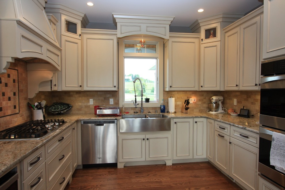Inspiration for a mid-sized transitional u-shaped medium tone wood floor eat-in kitchen remodel in Other with a farmhouse sink, recessed-panel cabinets, white cabinets, granite countertops, beige backsplash, subway tile backsplash, stainless steel appliances and no island