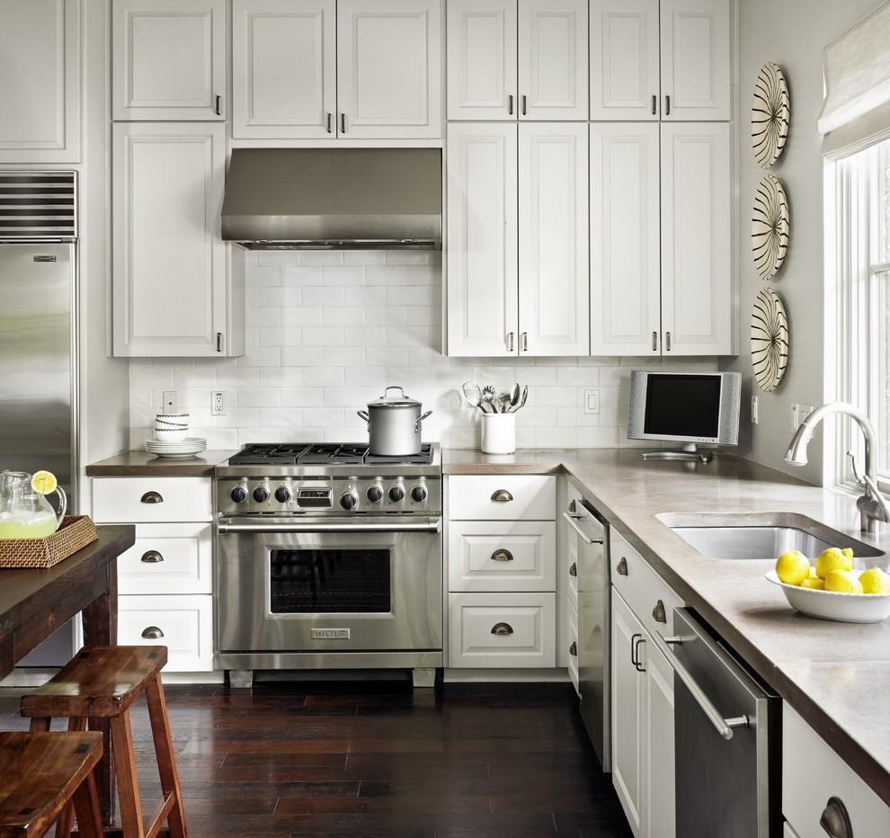 Elegant l-shaped kitchen photo in Austin with stainless steel appliances, subway tile backsplash, an undermount sink, concrete countertops, raised-panel cabinets, white cabinets and white backsplash