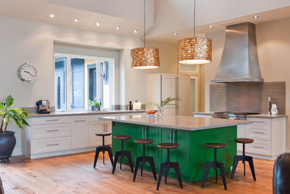 Inspiration for a contemporary l-shaped eat-in kitchen remodel in Vancouver with an undermount sink, recessed-panel cabinets, green cabinets, quartz countertops, gray backsplash, glass tile backsplash and paneled appliances