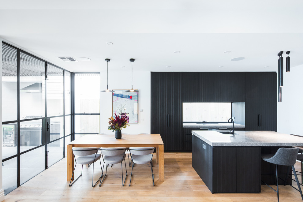 Example of a mid-sized trendy galley medium tone wood floor and brown floor open concept kitchen design in Melbourne with black cabinets, quartz countertops, window backsplash, black appliances, an island, gray countertops, an undermount sink and flat-panel cabinets