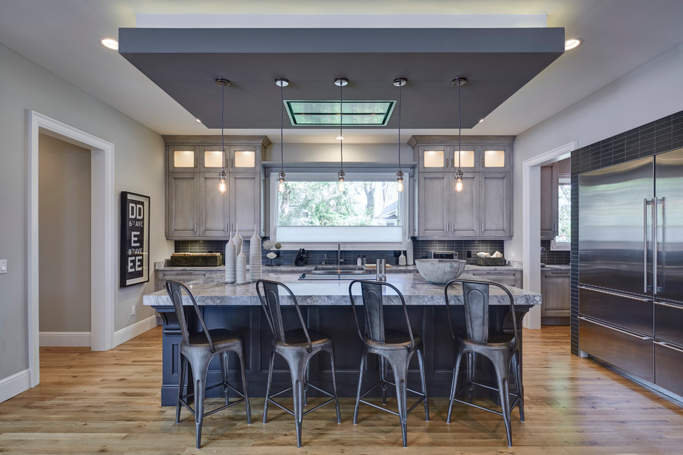 Example of a large urban l-shaped light wood floor open concept kitchen design in Detroit with quartzite countertops, gray backsplash, glass tile backsplash, stainless steel appliances, an island, distressed cabinets, a farmhouse sink and recessed-panel cabinets