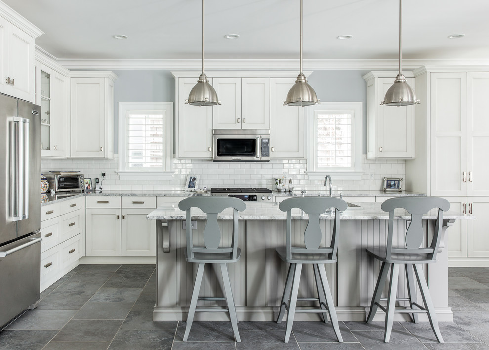 Inspiration for a large timeless l-shaped slate floor kitchen remodel in New York with white cabinets, granite countertops, white backsplash, subway tile backsplash, an island, stainless steel appliances and recessed-panel cabinets