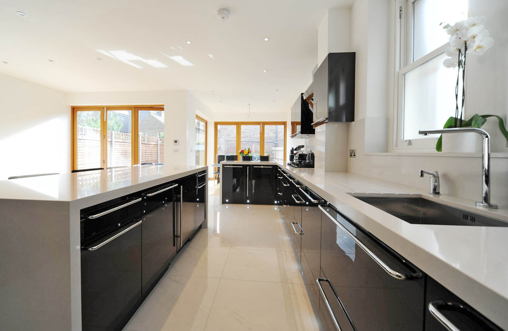 Minimalist kitchen photo in London with an undermount sink, flat-panel cabinets and black cabinets