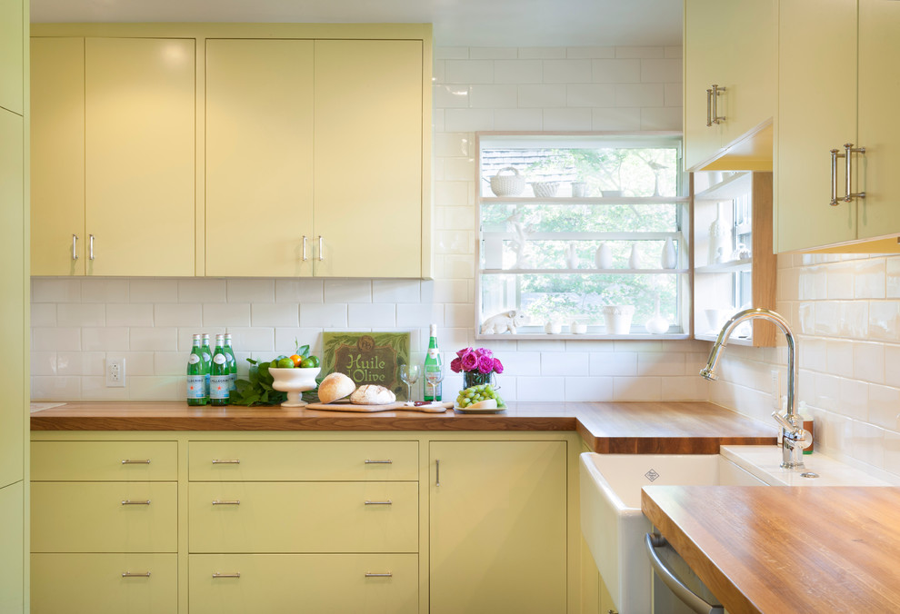 Inspiration for a contemporary enclosed kitchen remodel in Austin with a farmhouse sink, wood countertops, flat-panel cabinets, yellow cabinets, white backsplash and subway tile backsplash