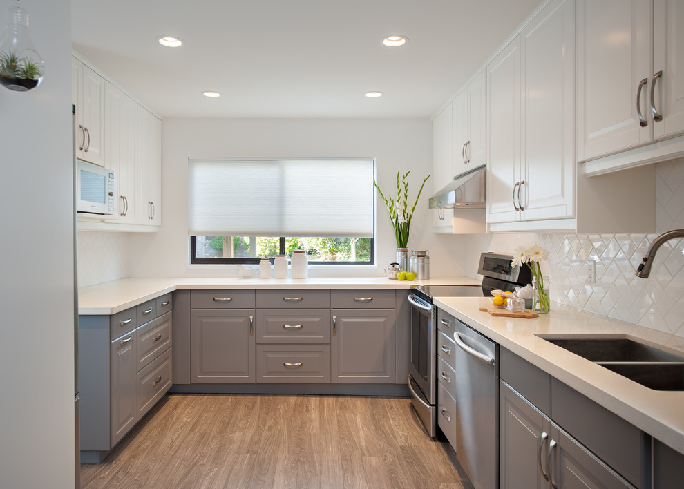 Enclosed kitchen - mid-sized traditional u-shaped enclosed kitchen idea in Vancouver with a double-bowl sink, raised-panel cabinets, gray cabinets, quartz countertops, white backsplash, subway tile backsplash, stainless steel appliances and no island