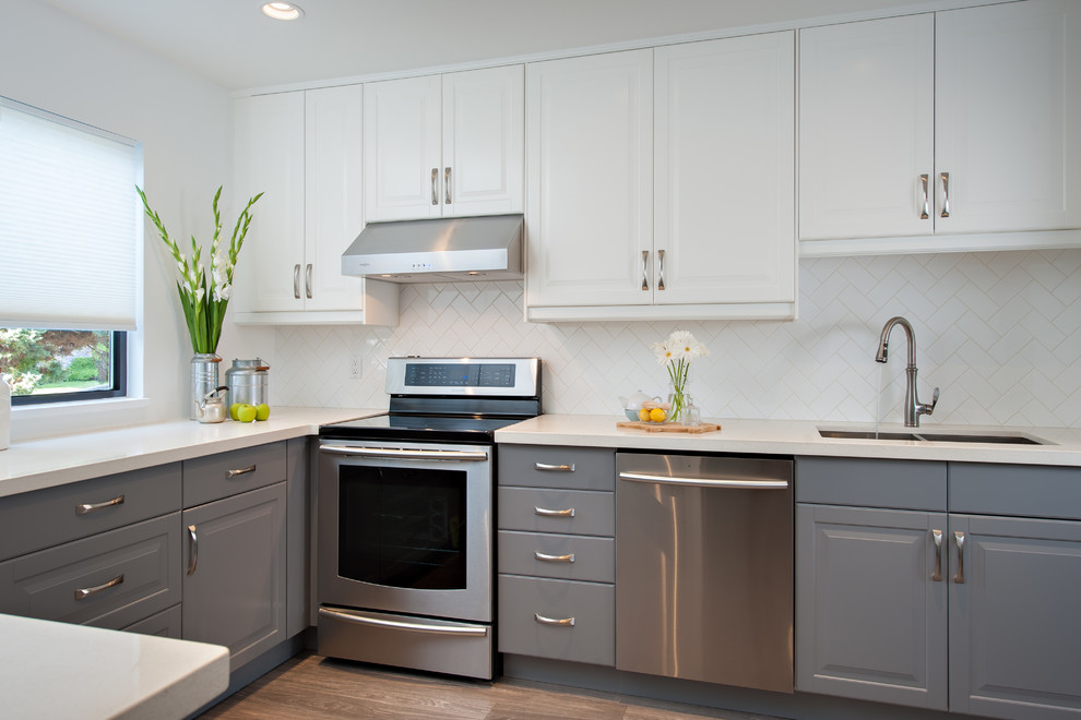Enclosed kitchen - mid-sized transitional u-shaped enclosed kitchen idea in Vancouver with a double-bowl sink, raised-panel cabinets, gray cabinets, quartz countertops, white backsplash, subway tile backsplash, stainless steel appliances and no island