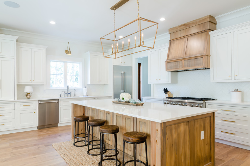 Kitchen - l-shaped light wood floor and beige floor kitchen idea in Miami with an undermount sink, shaker cabinets, white cabinets, stainless steel appliances, an island and white countertops