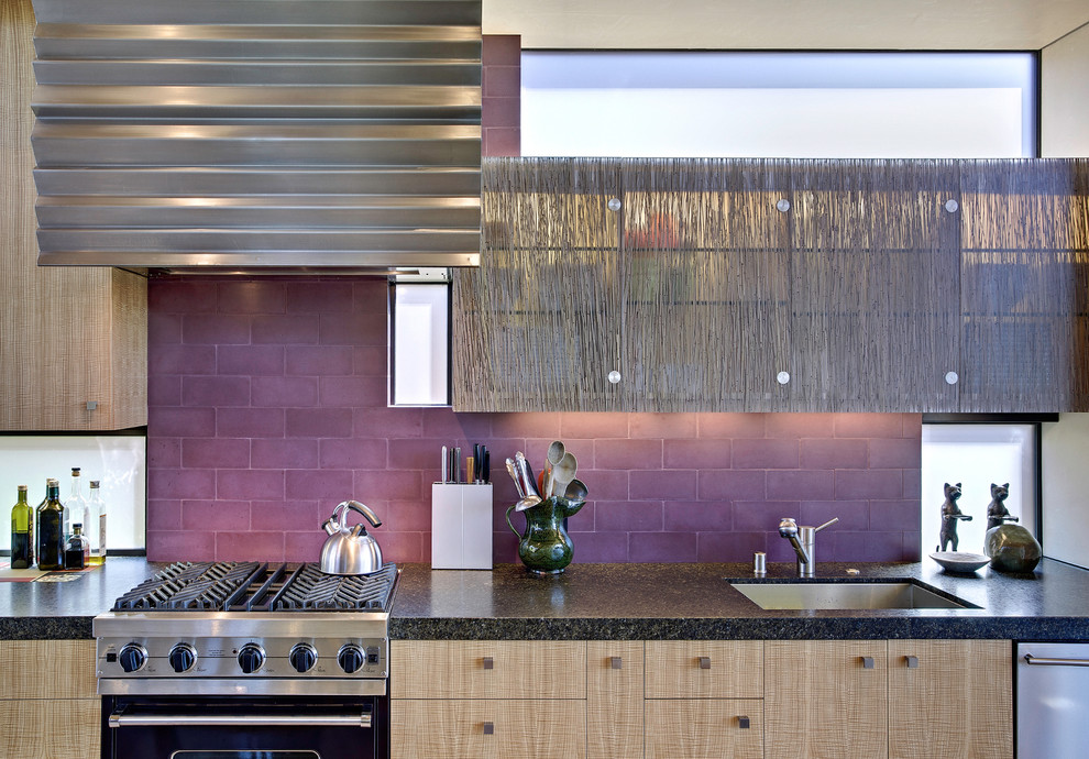 Example of a beach style galley eat-in kitchen design in San Francisco with subway tile backsplash, flat-panel cabinets, light wood cabinets, granite countertops, an undermount sink, black appliances and an island
