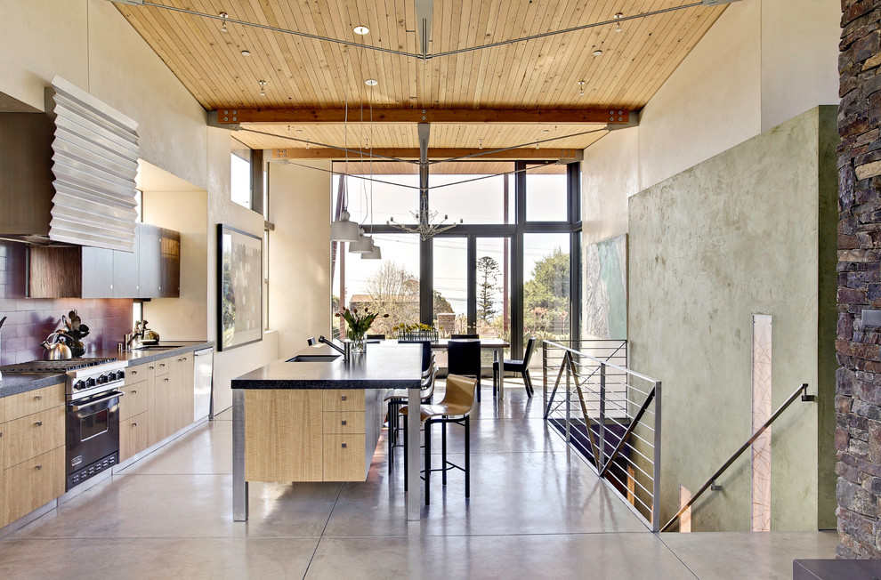 Example of a beach style galley concrete floor eat-in kitchen design in San Francisco with flat-panel cabinets, light wood cabinets, granite countertops, subway tile backsplash, black appliances, an undermount sink and an island