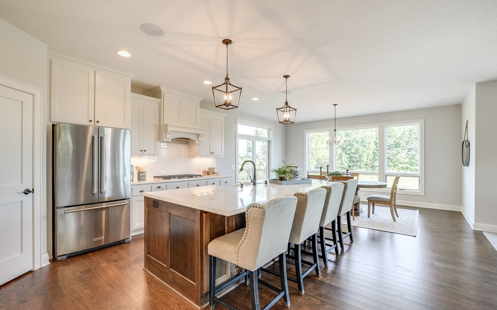 Inspiration for a large transitional galley medium tone wood floor and brown floor open concept kitchen remodel in Minneapolis with a farmhouse sink, white cabinets, quartz countertops, white backsplash, subway tile backsplash, stainless steel appliances, an island and shaker cabinets