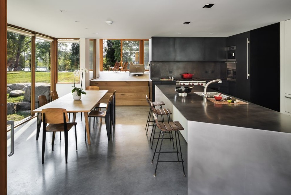Inspiration for a modern l-shaped eat-in kitchen remodel in New York with flat-panel cabinets, black cabinets and paneled appliances