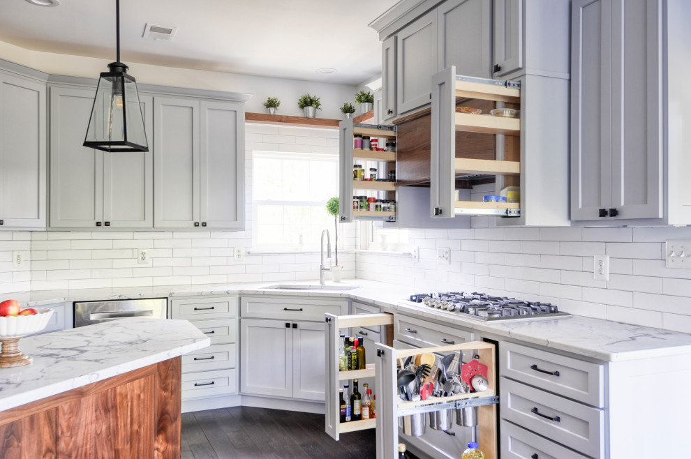Example of a mid-sized farmhouse u-shaped dark wood floor and brown floor eat-in kitchen design in DC Metro with an undermount sink, recessed-panel cabinets, gray cabinets, quartz countertops, white backsplash, subway tile backsplash, stainless steel appliances, an island and white countertops