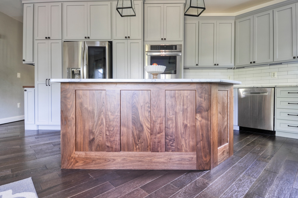 Inspiration for a mid-sized farmhouse u-shaped dark wood floor and brown floor eat-in kitchen remodel in DC Metro with an undermount sink, recessed-panel cabinets, gray cabinets, quartz countertops, white backsplash, subway tile backsplash, stainless steel appliances, an island and white countertops