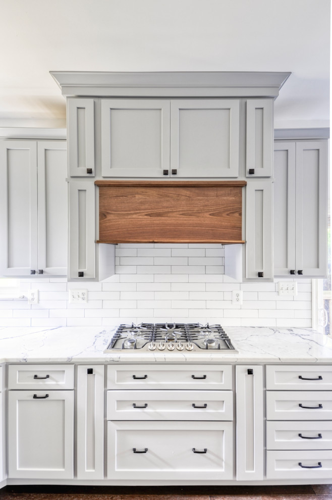 Example of a mid-sized country u-shaped dark wood floor and brown floor eat-in kitchen design in DC Metro with an undermount sink, recessed-panel cabinets, gray cabinets, quartz countertops, white backsplash, subway tile backsplash, stainless steel appliances, an island and white countertops