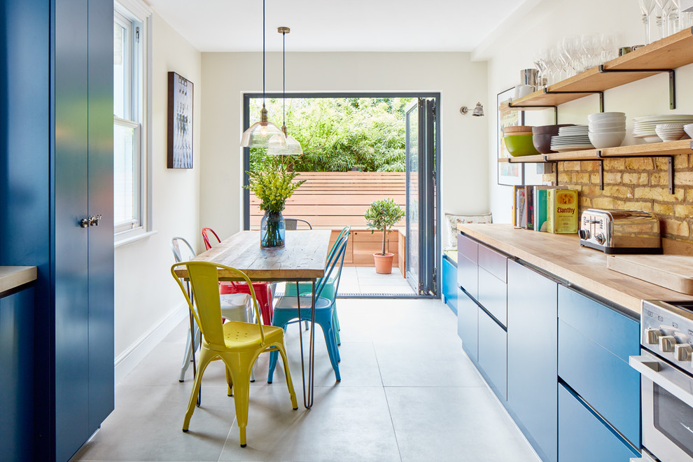 Inspiration for an eclectic eat-in kitchen remodel in London with flat-panel cabinets, blue cabinets, wood countertops, beige backsplash, stainless steel appliances and no island