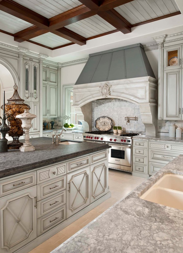 Inspiration for a mediterranean u-shaped enclosed kitchen remodel in Dallas with a double-bowl sink, recessed-panel cabinets, white cabinets, white backsplash, stone tile backsplash and an island